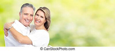 Happy senior couple. - Happy senior loving couple over green...