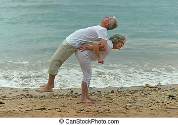 couple having fun - Happy senior couple having fun on beach