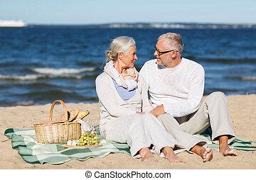happy senior couple having picnic on summer beach - family,...