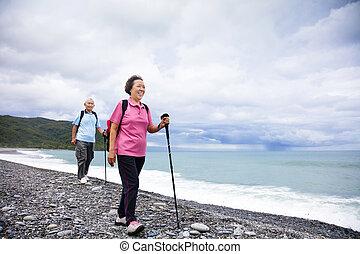 happy senior couple hiking on the coast beach