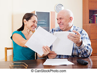 Happy senior couple holding  documents at home
