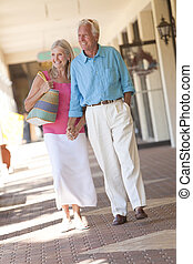 Happy Senior Couple Holding Hands in Shopping Mall