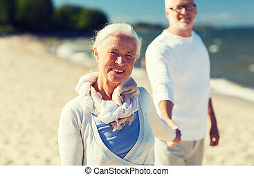 happy senior couple holding hands on summer beach - family,...