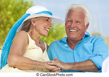 Happy Senior Couple Holding Hands & Laughing at the Beach -...