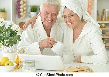 senior couple in a bathrobes with laptop