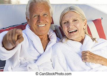 Happy Senior Couple In Bathrobes at Health Spa - Happy...