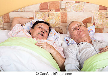 Happy senior couple in bed