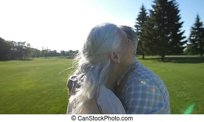 Happy senior couple in love hugging on green lawn