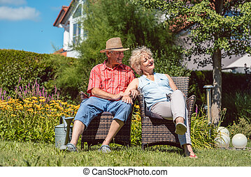 Happy senior couple in love relaxing together in the garden in a