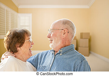Happy Senior Couple In Room with Moving Boxes on Floor -...