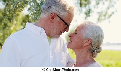 happy senior couple kissing at summer park - old age, love...