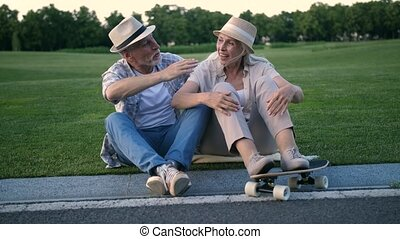 Happy senior couple laughing after skateboarding