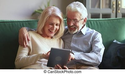 Happy senior couple laughing relaxing on sofa using digital tablet