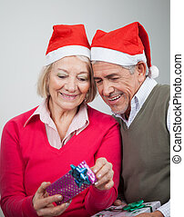 Happy Senior Couple Looking At Christmas Gifts