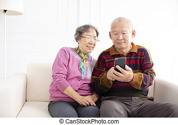 happy senior couple looking at mobile phone