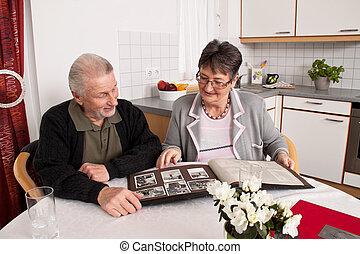 Happy senior couple looking at photo album.