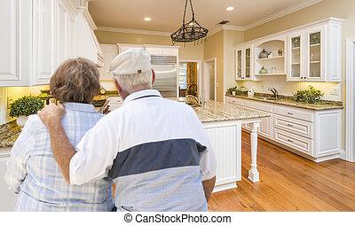 Senior Couple Looking Over Beautiful Custom Kitchen