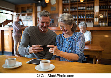 Happy senior couple looking their photos on mobile phone