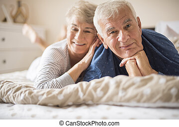 Happy senior couple lying down on the bed