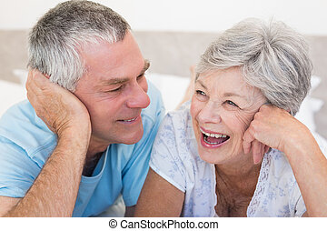 Happy senior couple lying on bed together at home