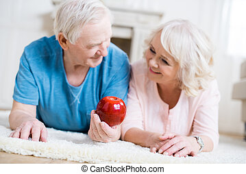 Happy senior couple lying on carpet with big red apple