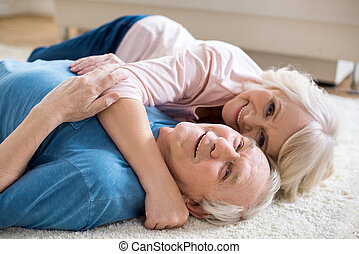 Happy senior couple lying together on carpet and hugging