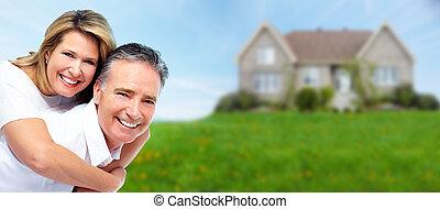 Happy senior couple near new house. Real estate background.