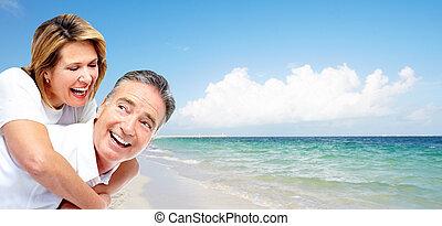 Happy senior couple on a tropical beach. Caribbean vacation resort.