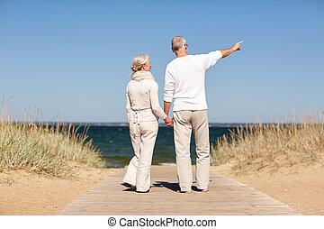 happy senior couple on summer beach