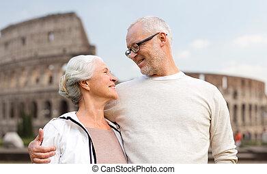happy senior couple over coliseum in rome, italy - family,...