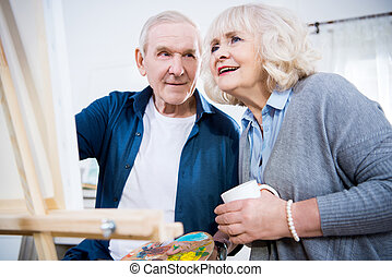 Happy Senior Couple Painting Picture Together At Home