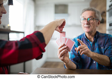 Happy senior couple playing cards together
