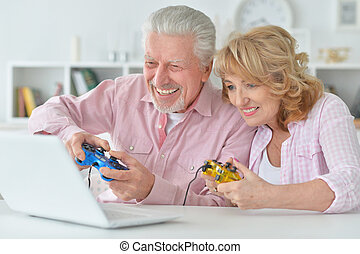 happy senior couple playing computer game at home