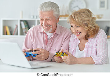happy senior couple playing computer game
