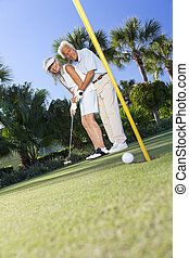 Happy Senior Couple Playing Golf Putting on Green