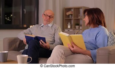 happy senior couple reading books at home - relationships, ...