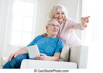 Happy senior couple relaxing at home, woman pointing