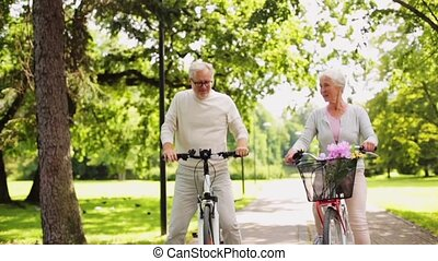 happy senior couple riding bicycles at summer park - active...