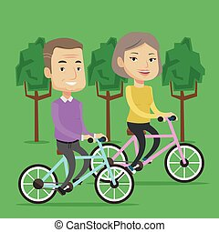 Happy senior couple riding on bicycles in the park