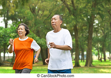 happy senior couple running together in the park