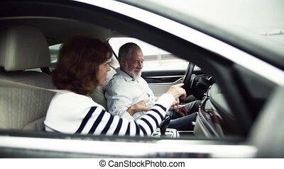 Happy senior couple sitting in car, talking. Slow motion. -...