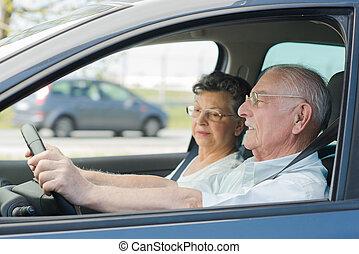 happy senior couple sitting inside car