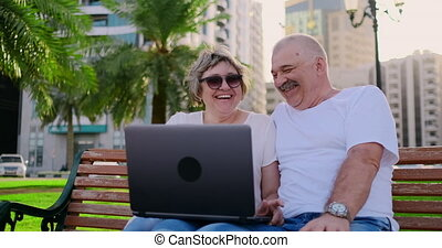 Happy senior couple sitting on a bench in the summer in a modern city with a laptop among the palm trees on the background of skyscrapers