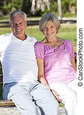Happy Senior Couple Sitting on Bench in Sunshine