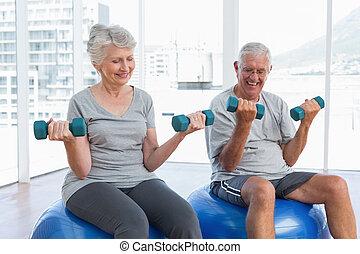 Happy senior couple sitting on fitn
