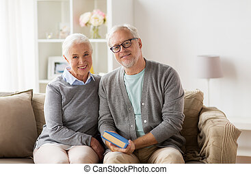 happy senior couple sitting on sofa at home - relationships,...