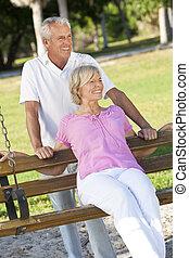 Happy Senior Couple Smiling Outside in Sunshine on Park Swing