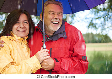 Happy senior couple standing during rain