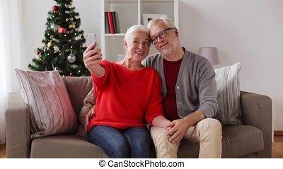 happy senior couple taking christmas selfie - christmas,...