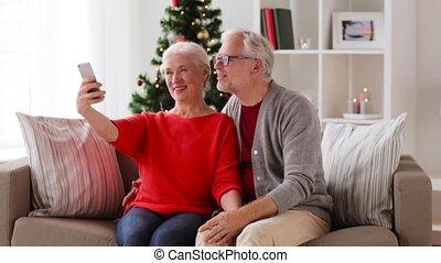 happy senior couple taking christmas selfie